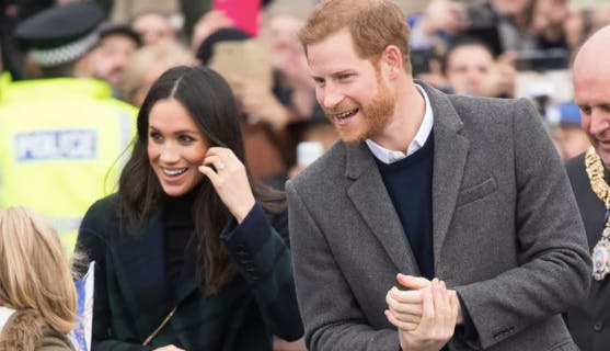 Prince Harry leaning into Meghan Markle