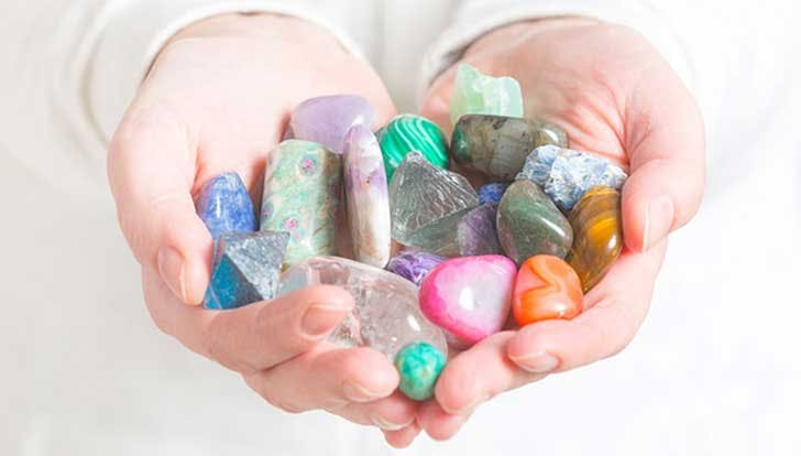 Woman holding hand full of healing crystals