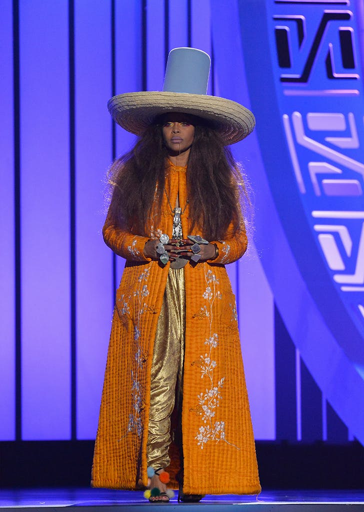 erykah badu wearing an orange coat and tall hat