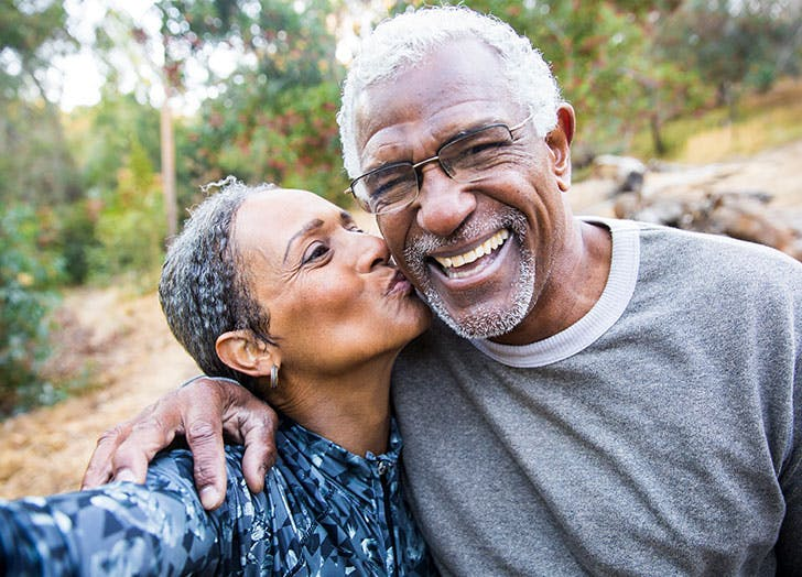 happy older couple kissing selfie