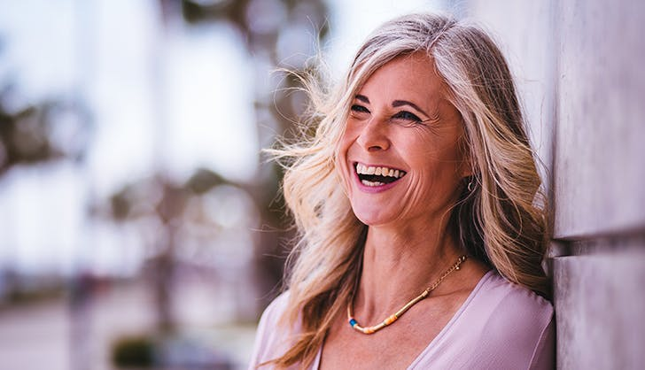 middle aged woman with long gray hair laughing