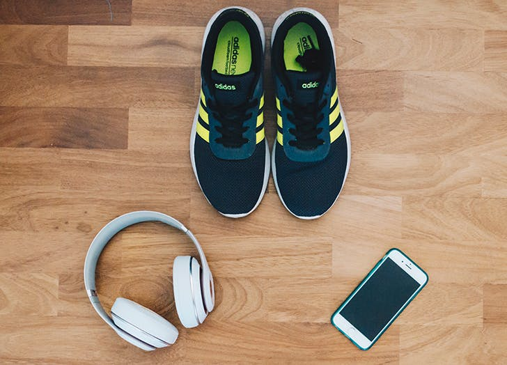 sneakers on the floor next to headphones and a phone