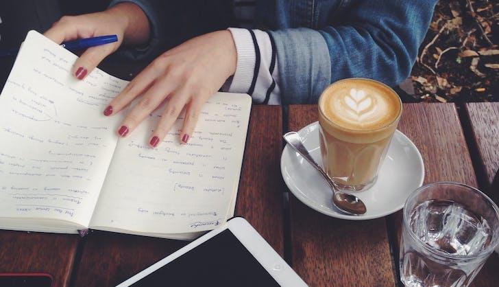 teenage girl doing work at a coffee shop