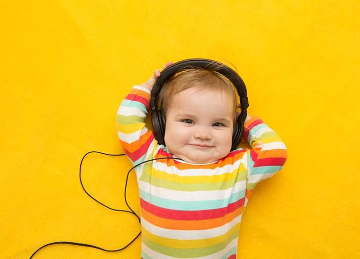 the baby with headphones on a yellow background