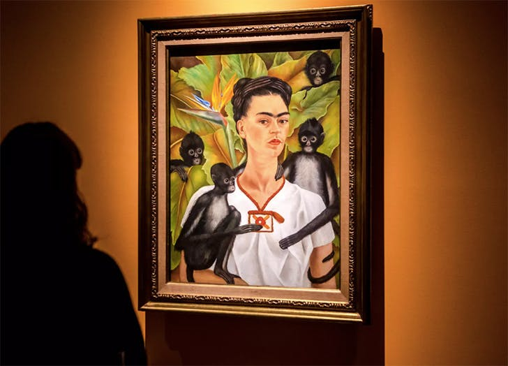 woman looking at a painting with frida kahlo