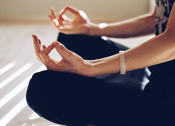 woman sitting on the floor meditating