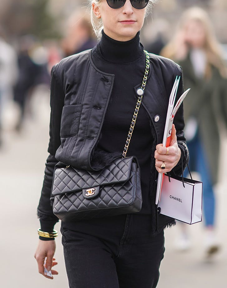 woman wearing a black outfit with a black quilted chanel bag