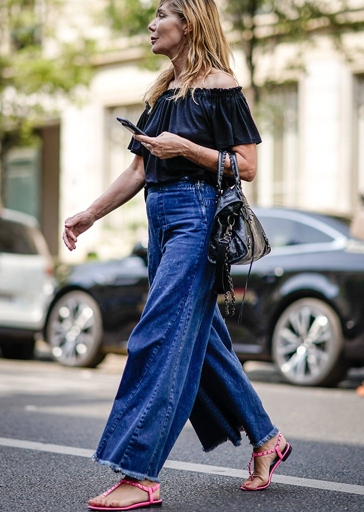 woman wearing an off the shoulder top and wide leg jeans