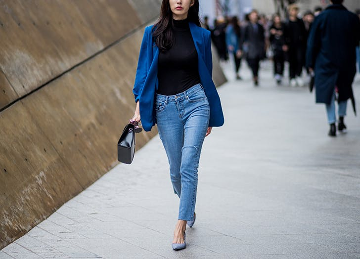 woman wearing jeans black turtleneck and blue blazer