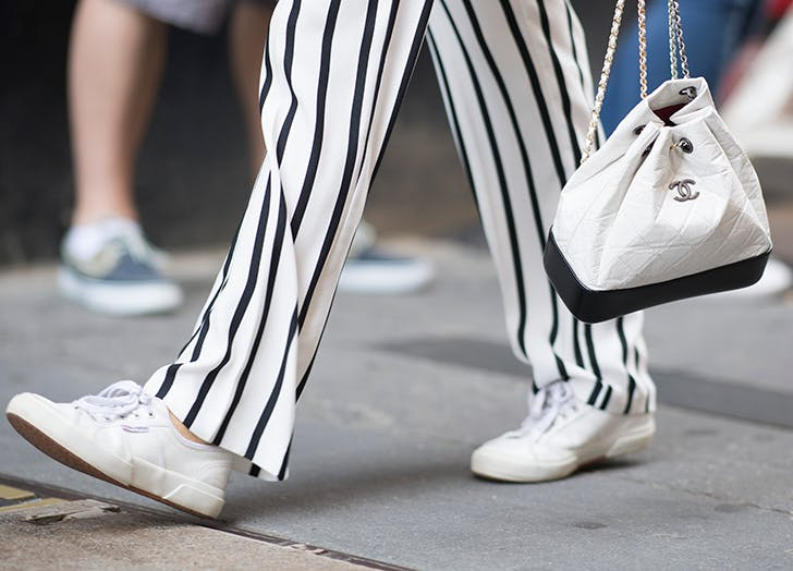 woman wearing striped pants and white sneakers