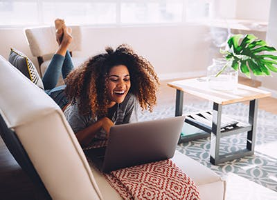 woman smiling using laptop at home 400
