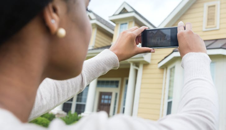 woman taking a photo of a house on the market she wants to buy