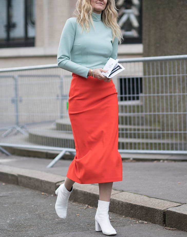 woman wearing mint green and a red skirt