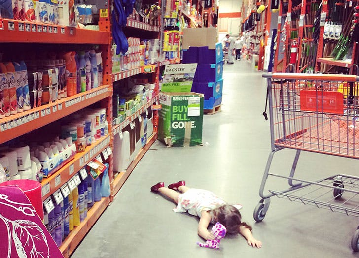 young girl laying on a floor at a store