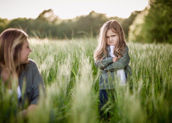 young girl pouting in a field