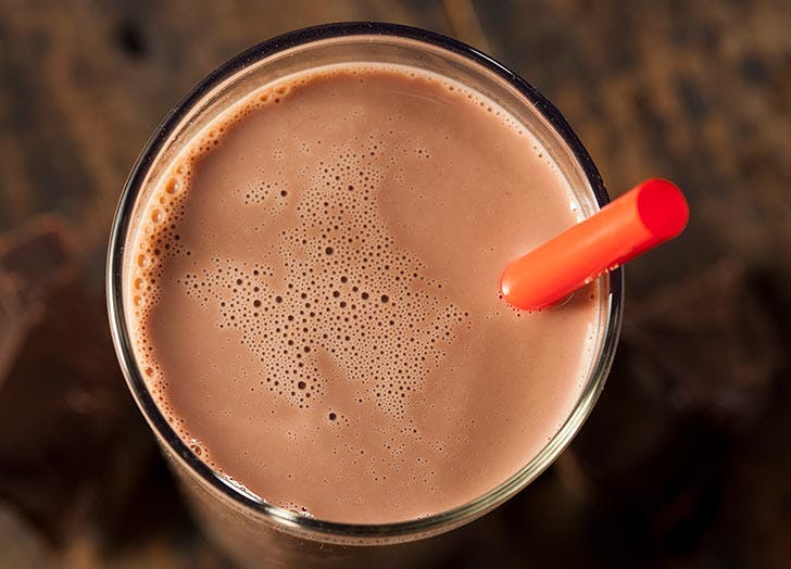 Chocolate milk on a glass with red straw