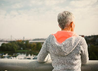 Older woman practicing mindfullness in city 400