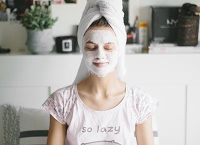 Woman doing face mask lazy self care 400