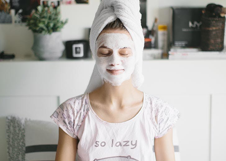 Woman doing face mask lazy self care