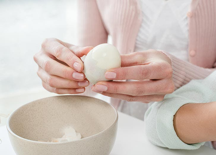 Woman peeling hard boiled egg