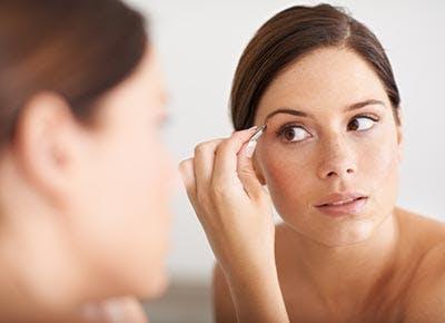 Woman tweezing eyebrows 400
