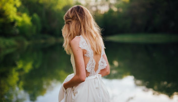 bride posing in her dress by a lake