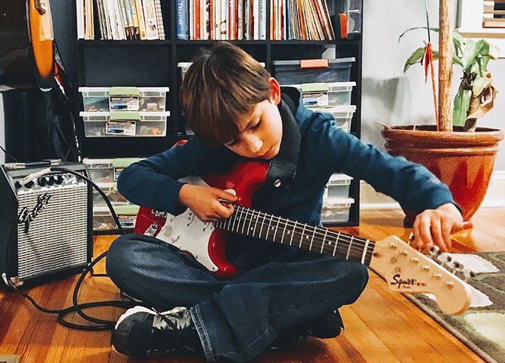 kid tuning a guitar