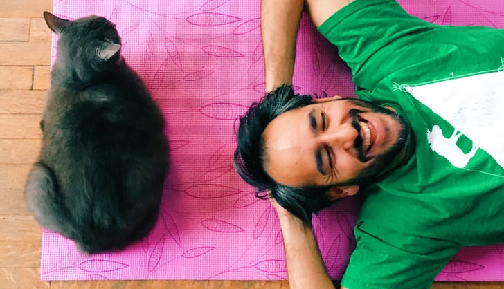 man laughing with his cat on a yoga mat