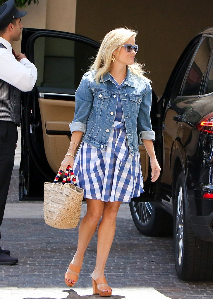 reese witherspoon wearing a gingham dress and jean jacket