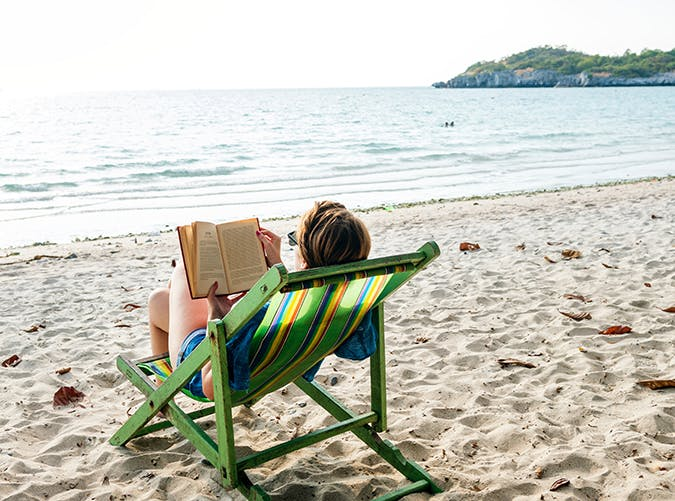 woman reading a book on the beach