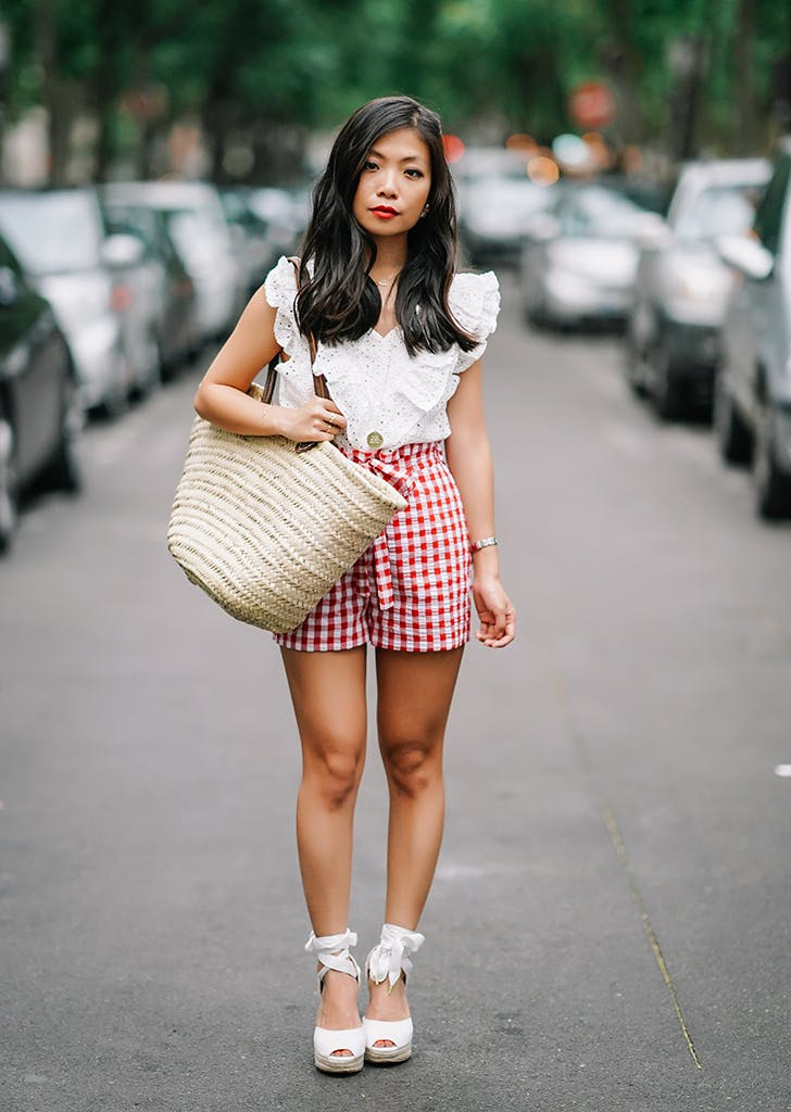 woman wearing a white top and red gingham shorts