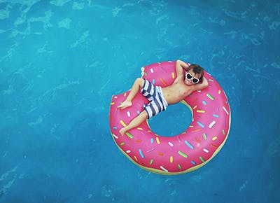 Kid floating in donut pool float cat