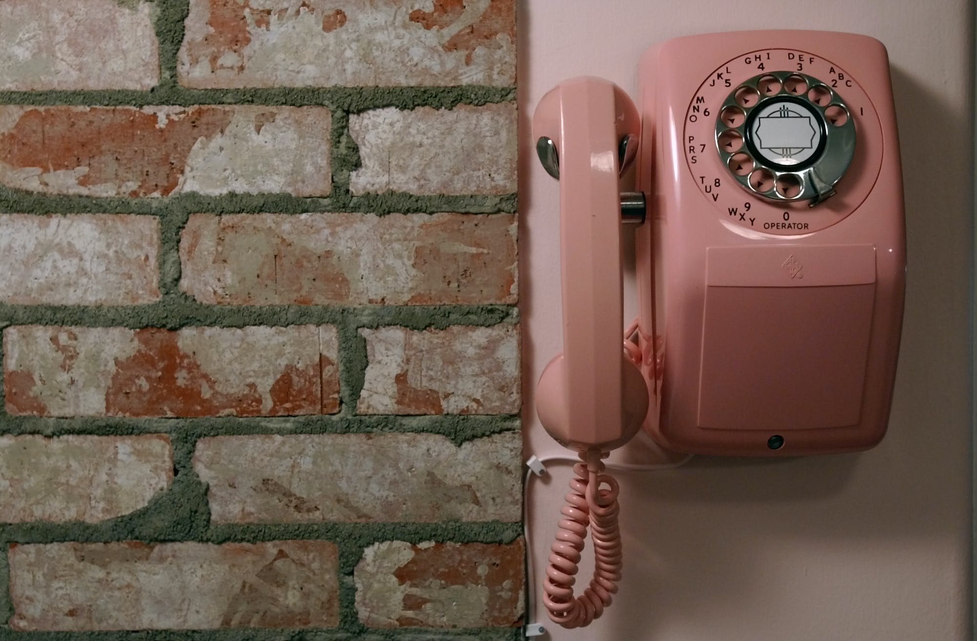 a pink rotary phone mounted on the kitchen wall