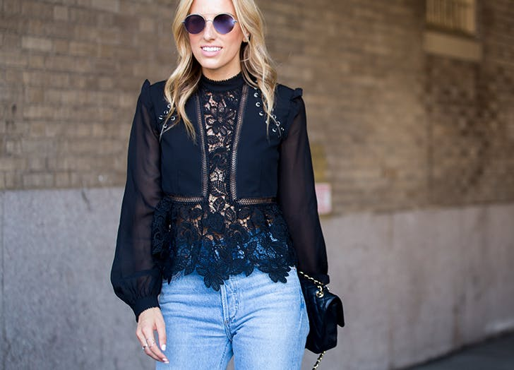 a woman wearing a black lace blouse with jeans