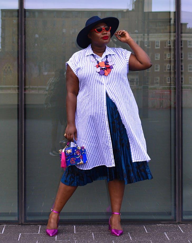 a woman wearing a shirtdress over another dress