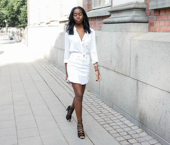 a woman wearing a white denim skirt