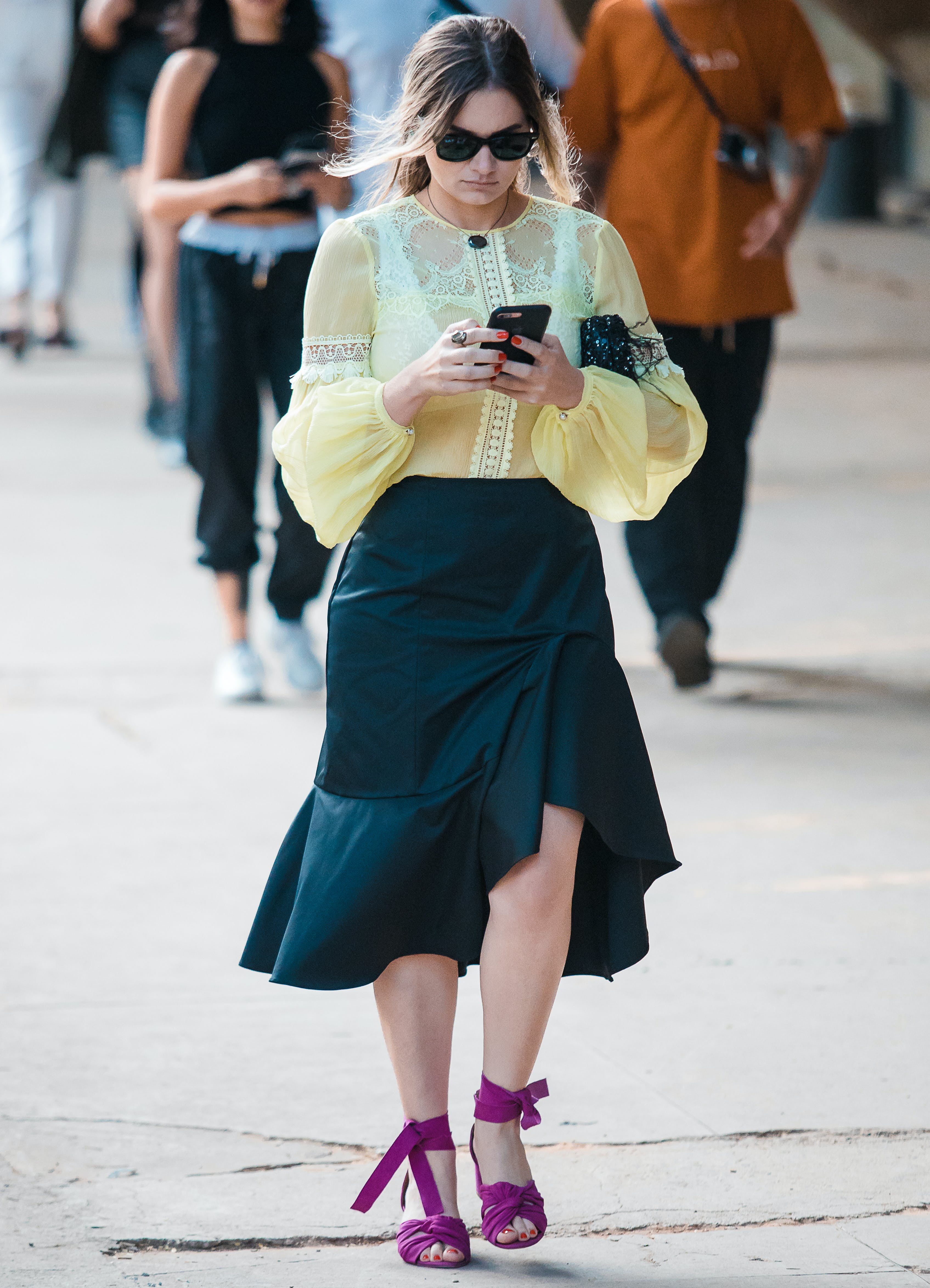 a woman wearing a yellow top and purple sandals