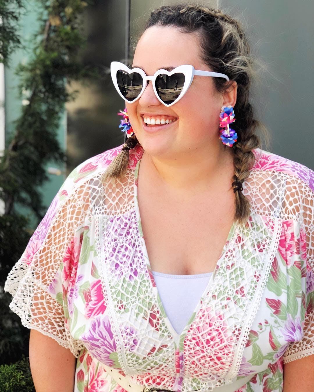 a woman wearing fun heart shaped sunglasses