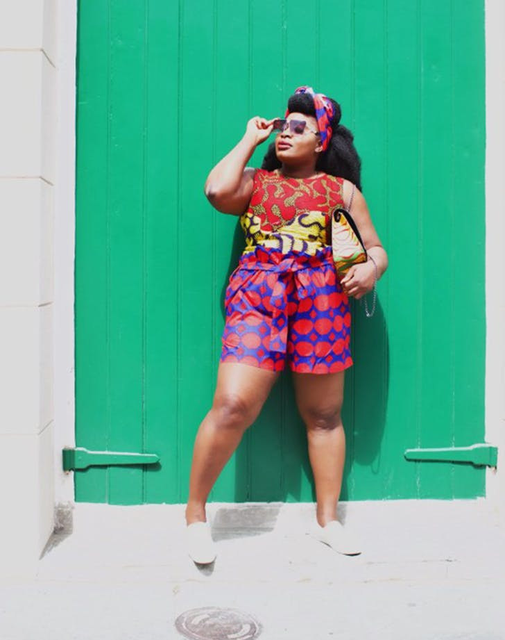 a woman wearing multiple bold prints at once