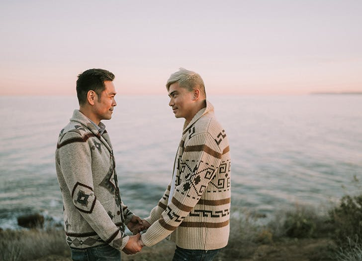 couple holding hands wearing sweaters at the beach