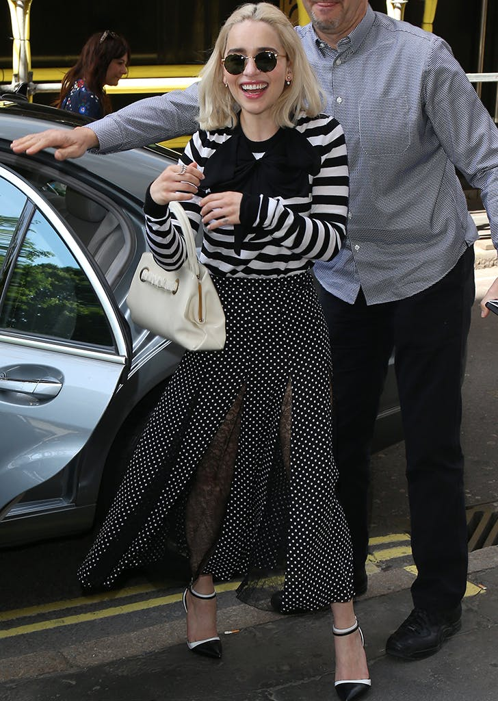 emilia clarke wearing a striped top and skirt