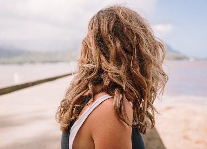 girl back of head beach waves