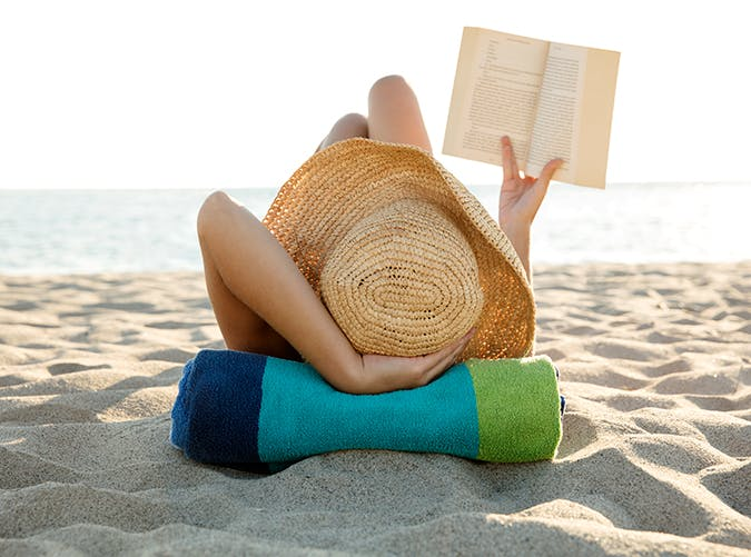 woman lying on the beach reading a book