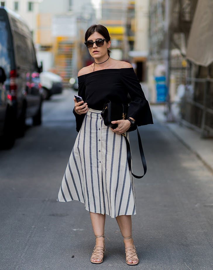 woman wearing an off the shoulder top and striped skirt