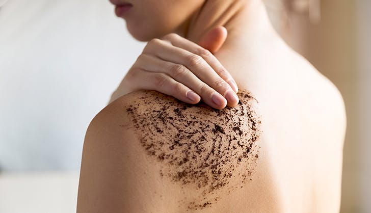 woman applying coffee scrub