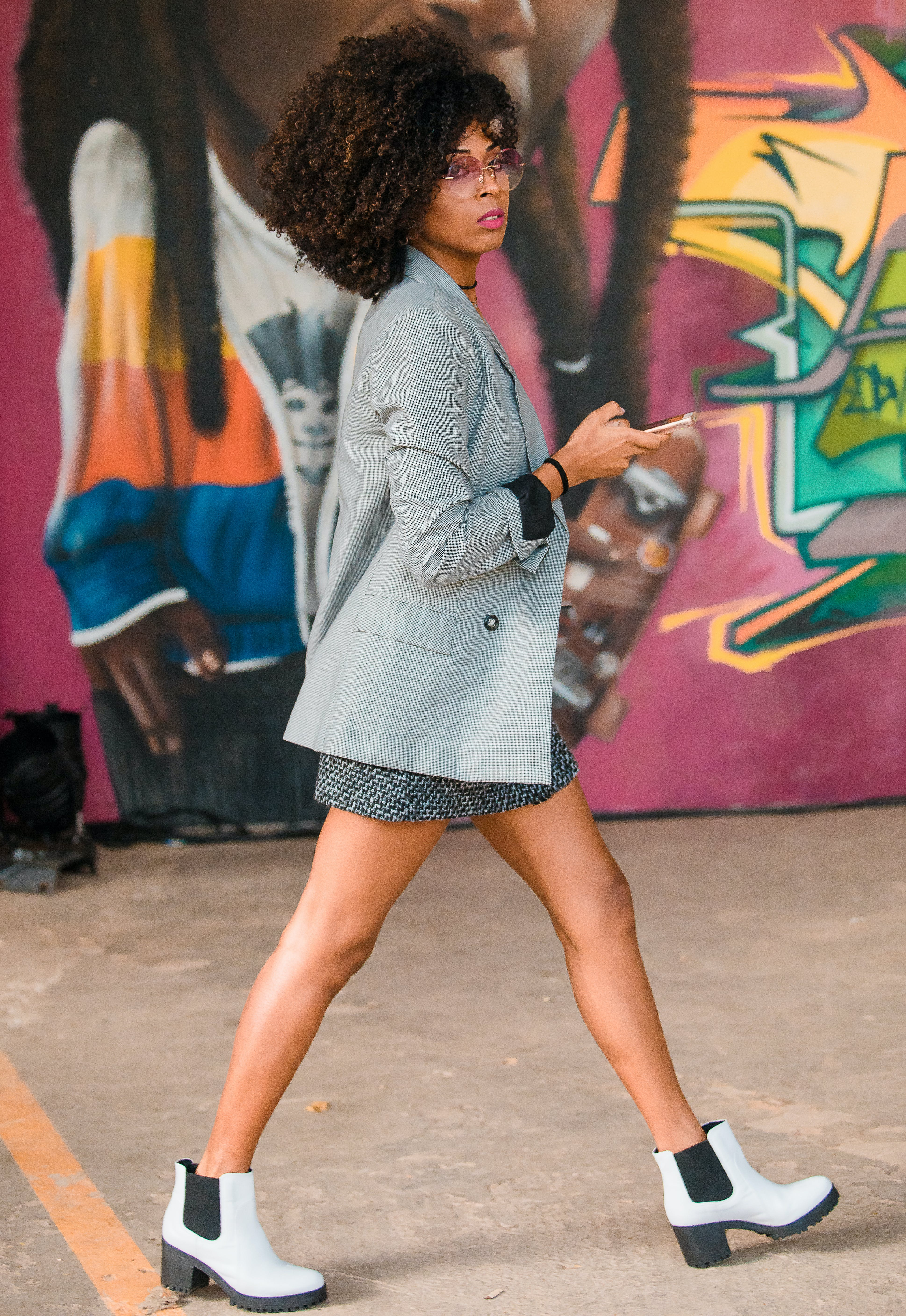 woman wearing white ankle boots with a mini skirt in summer