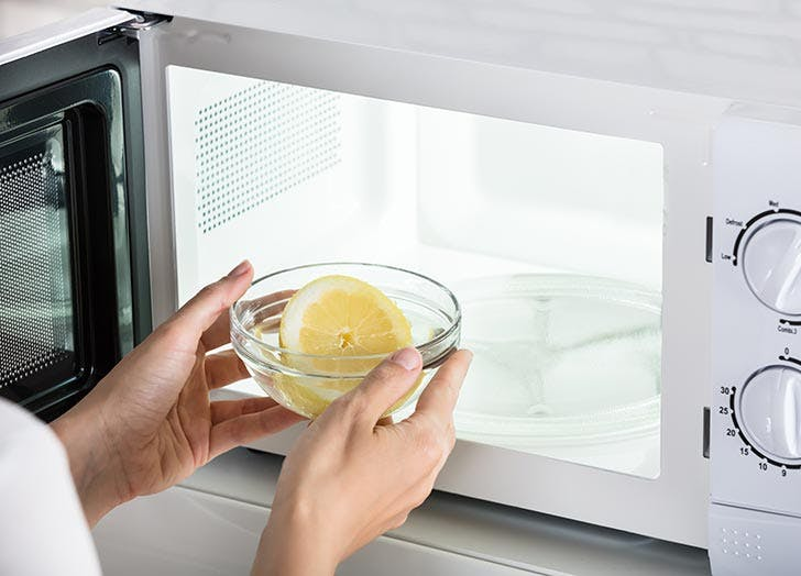Woman cleaning her microwave with lemon