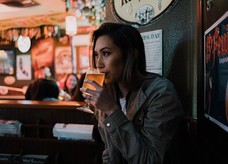 girl drinking a beer alone