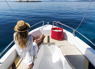 girl on boat red bag hat 400