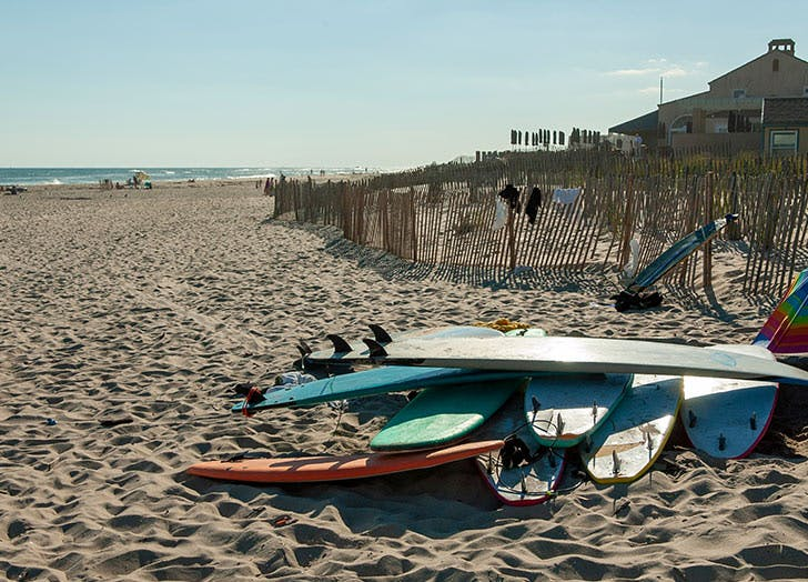 pile of surf boards on beach